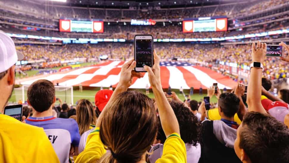 A group of people in a football stadium holding their cell phones up.