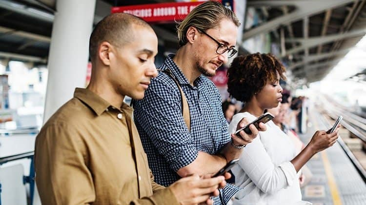 A group of people looking at their cell phones while waiting for their train.