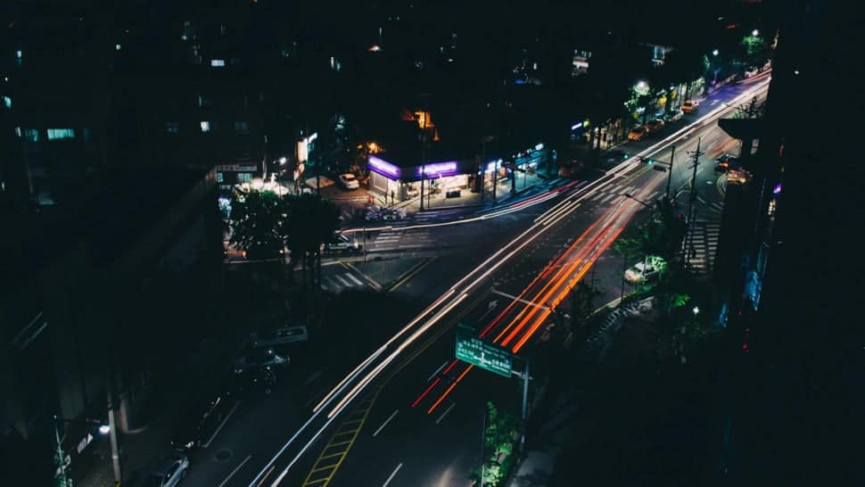 A photo of a busy street in a city at night.
