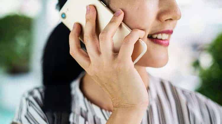 Businesswoman at home holding a cell phone while talking to someone.