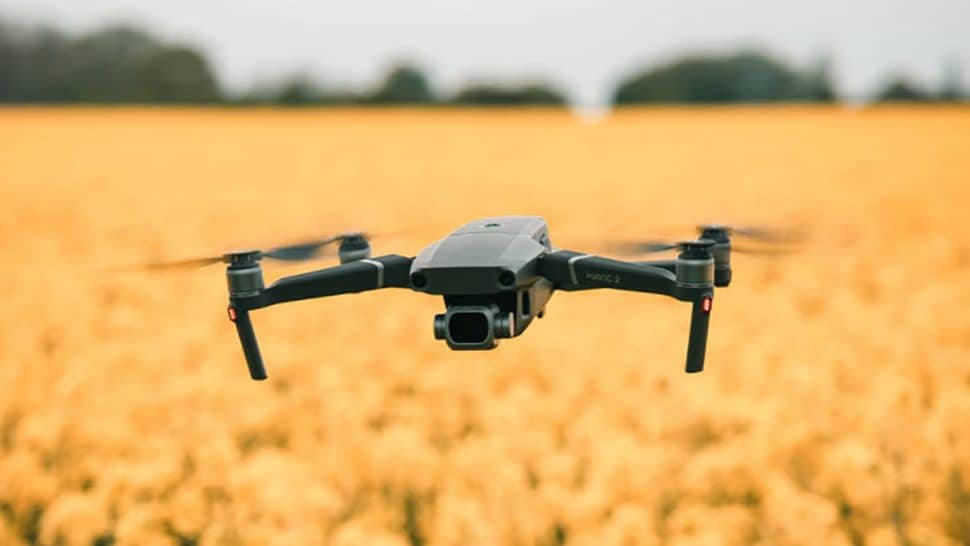 Image of a drone flying in a field with yellow flowers