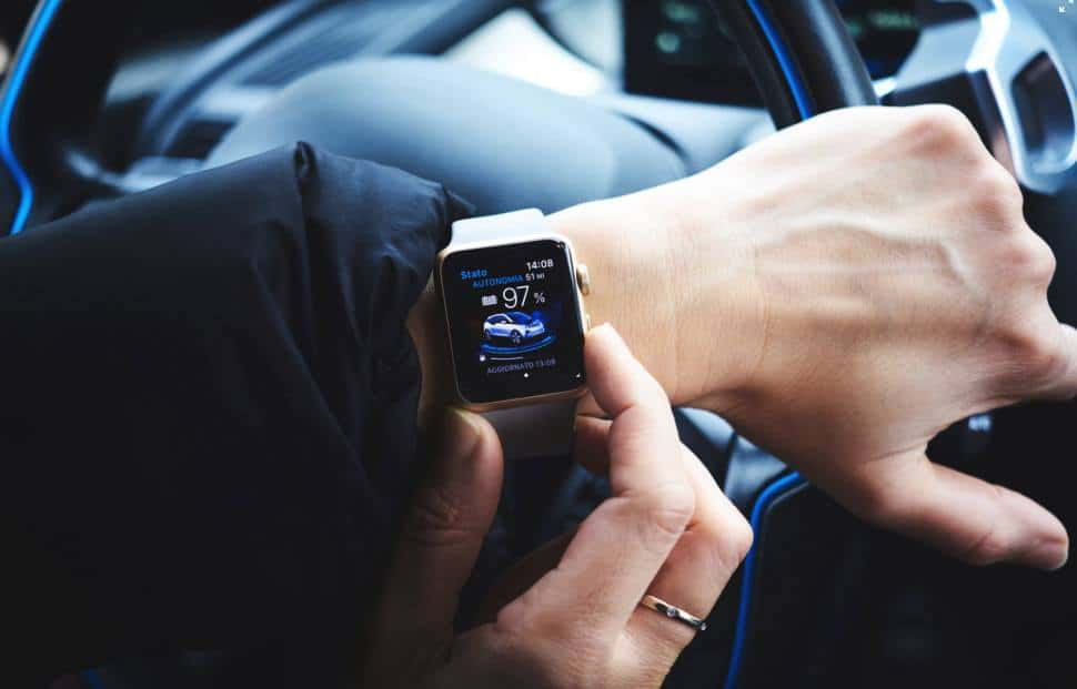 Image of a person in a car using a smartwatch while holding the car wheel.
