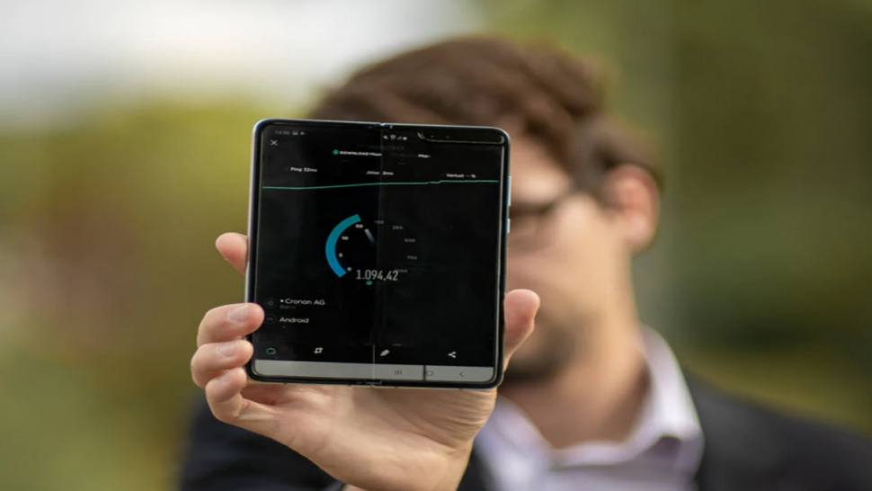 Man holding a 5g device that is presenting a timer on the screen.