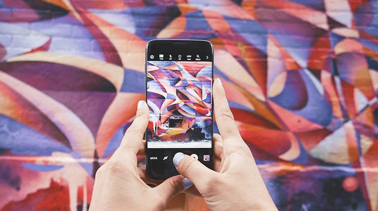 Someone is holding an iPhone in front of a wall with graffiti art.